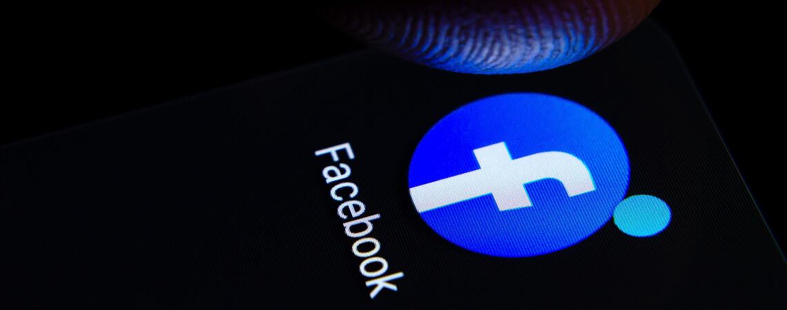 Facebook-Logo auf Bildschirm vor dunklem Hintergrund