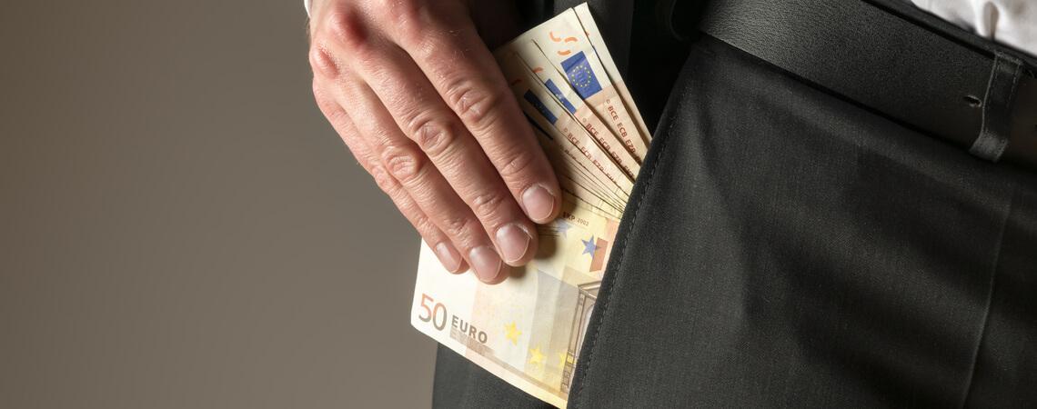 Mann steckt sich Geld in Tasche