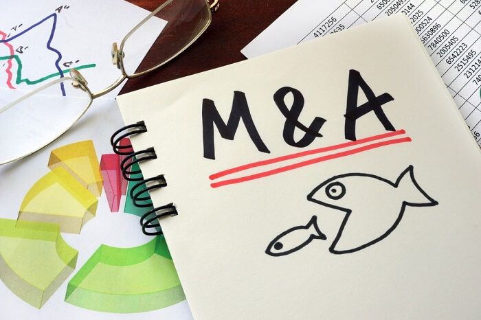 M&A Merger And Acquisitions written on a notepad